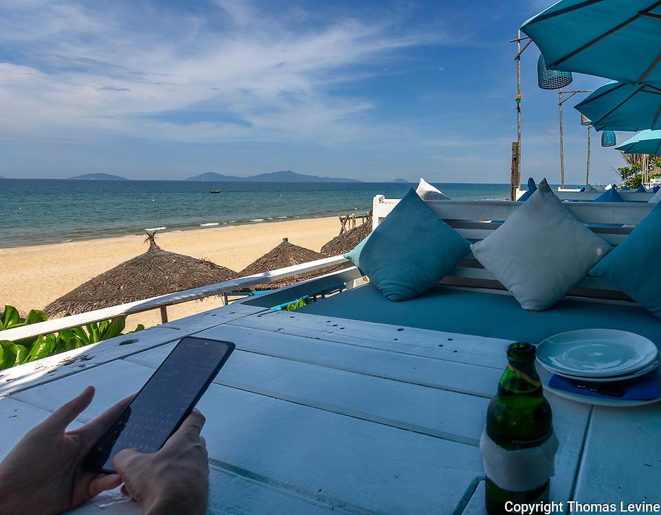 Deckhouse lounging with a beer overlooking the beach and ocean with Cham Island.