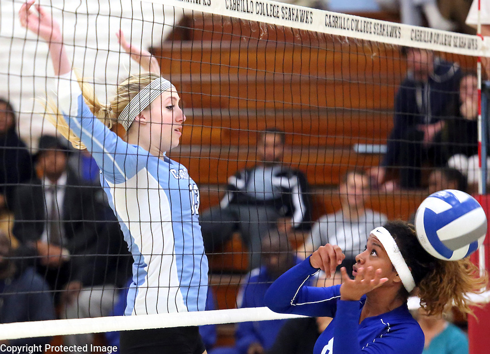 Cabrillo College 5'11'' freshman middle blocker Madison Borch, left, floats back to earth after rejecting a shot from Alameda's Christina Curry during Cabrillo's 3-game victory in the first round of the Northern California playoffs in Aptos, California. Cabrillo is the #1 ranked women's volleyball team in the state. <br /> Photo by Shmuel Thaler <br /> shmuel_thaler@yahoo.com www.shmuelthaler.com
