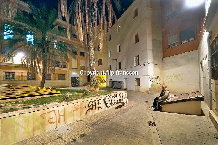 Spanje, Va,encia, 3-11 2019Een oudere man laat zijn hond uit in het binnentuintje van zijn appartementengebouw in het oude centrum, stadscentrum, van de stad . Hij is niet meer goed ter been en laat de hond daarom steeds het balletje wat hij weggooit terugbrengen . Foto: Flip Franssen