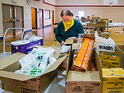 06 APRIL 2020 - DES MOINES, IOWA: GLENNA CALHOUN, a volunteer, packs food boxes before a drive through emergency food distribution at First DSM Church in Des Moines. On Monday, 06 April, Iowa reported 946 confirmed cases of the Novel Coronavirus (SARS-CoV-2) and COVID-19. There have been 25 deaths attributed to COVID-19 in Iowa. Most non-essential businesses are closed until 30 April. Well over 100,000 Iowans filed first time claims for unemployment in the last three weeks, more than applied during the peak of the Great Recession of 2008. Local food banks have seen an equal spike in people seeking nutritional assistance. First DSM Church has increased their food pantry from one day weekly to three days per week. Hundreds of people lined up Monday to get a box of food and one roll of toilet paper at the church's drive through pantry.           PHOTO BY JACK KURTZ