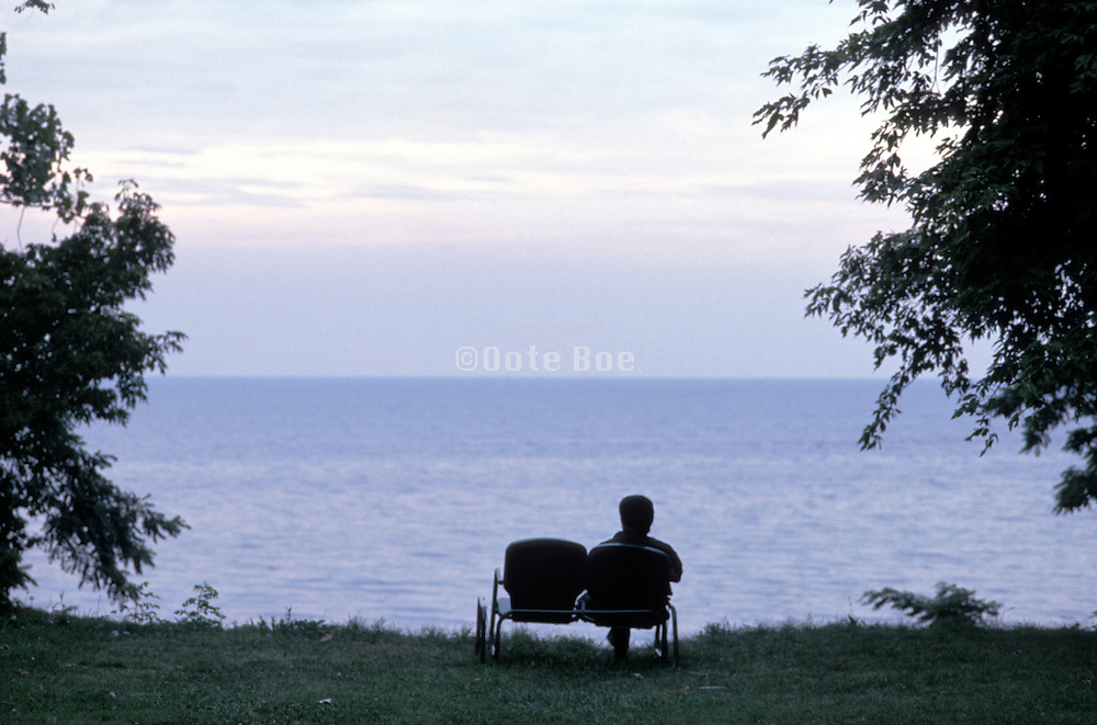 silhouetted solitary seated figure overlooking water
