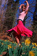 A912M3 Girl dancing in daffodil woods in spring time