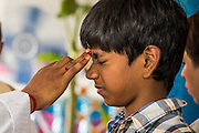 """29 SEPTEMBER 2012 - NAKORN NAYOK, THAILAND:  A boy winces as a Brahman priest anoints him during observances of Ganesh Ustav at Wat Utthayan Ganesh, a temple dedicated to Ganesh in Nakorn Nayok, about three hours from Bangkok. Many Thai Buddhists incorporate Hindu elements, including worship of Ganesh into their spiritual life. Ganesha Chaturthi also known as Vinayaka Chaturthi, is the Hindu festival celebrated on the day of the re-birth of Lord Ganesha, the son of Shiva and Parvati. The festival, also known as Ganeshotsav (""""festival of Ganesha"""") is observed in the Hindu calendar month of Bhaadrapada, starting on the the fourth day of the waxing moon. The festival lasts for 10 days, ending on the fourteenth day of the waxing moon. Outside India, it is celebrated widely in Nepal and by Hindus in the United States, Canada, Mauritius, Singapore, Thailand, Cambodia, Burma , Fiji and Trinidad & Tobago.     PHOTO BY JACK KURTZ"""