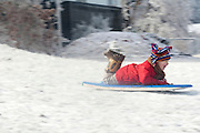 A boy ride a toboggan down an icy hill while playing in winter weather.