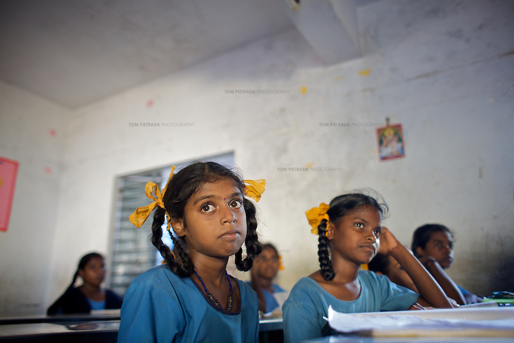 """Vijyashree (foreground) in class at the Government Girls High School, Venugopalapuram in Cuddalore.. .Vijita (age 14) and Vijyashree (age 11) Viswanathan lost their mother and brother to the tsunami in 2004. They continue to live in the fishing village of Thazanguda with their father Viswanathan, his second wife Kayalvizhi and their two children Sanjay (age 3) and Monica (age 1). ..Until the beginning of the 2009 academic year in June, Vijita and Vijyashree attended the local Thazanguda school. This village school teaches pupils only until the 8th Standard and with Vijita now entering the 9th, it was decided that the two daughters remain together and both travel 3km to the local town school: the Government Girls High School, Venugopalapuram in Cuddalore. ..At the same time Viswanathan decided he would cease day-to-day care of his daughters and place them in the Government Home for Tsunami Children, also in Cuddalore. This was not a move welcomed by either Vijita or Vijyashree and one afternoon after just two weeks at the orphanage, the two girls ran away. At roll call in the orphanage that evening the alarm was sounded and the two sisters were eventually located in Thazanguda waiting for their father and Kayalvizhi who were both away at the time. Realising his daughters' unhappiness, Viswanathan then took them out of the Government home. ..According to her class teacher, Vijita often compares her step-mother to her mother and concludes that she wants her mother back. Vijita confides in her teachers that her stepmother is forever demanding that she and her sister Vijyashree undertake housework. This frustration at home is tempered by the genuine love both sisters have for their father and two younger siblings Sanjay and Monica. Vijita expresses a lonelyness without her mother. Pushpavalli concludes that """"Vijita wants something else beyond the love of her father and sister"""". ..Viswanathan appears genuinely to want the best for his two elder daughters. His experiment e"""