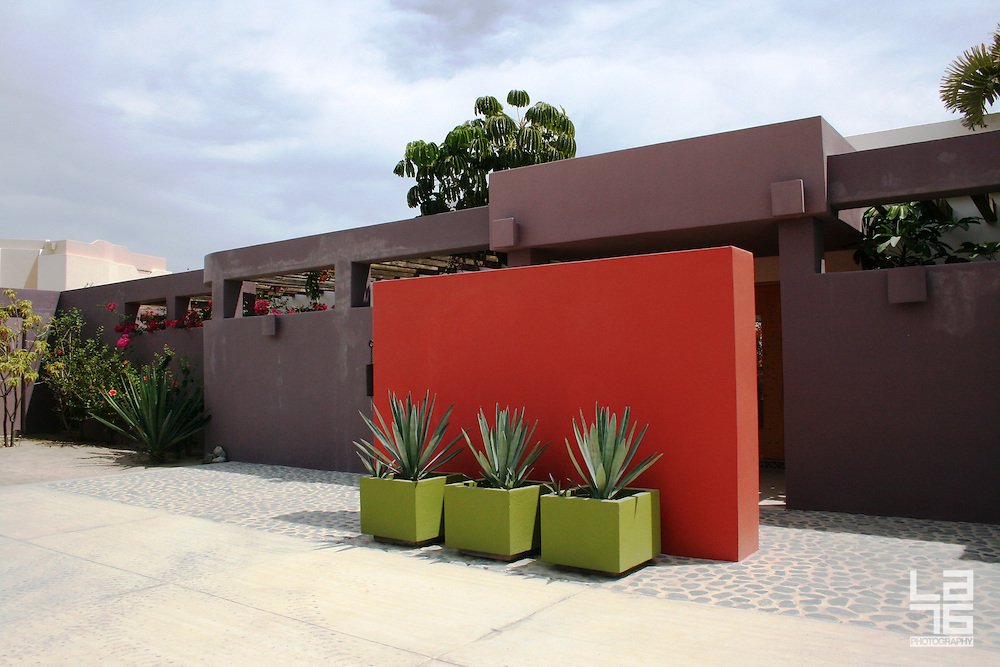 Interior patio in a minimalistic Mexican home, with purple walls, and a red wall with three agave plants in green planters. <br /> Photo shooting took place in a modern, minimalistically decorated beachfront home in exotic small town of Los Barriles, Baja California Sur, Mexico. <br /> Home decoration is comprised of different color selections, each used with careful combination of details and accompanying furniture, plants and other decorative elements. Prevailing colors are white, red and striking turquoise blue.<br /> Here we are showing photographs from 2 parts of this home; guest bedroom and inner patio, where magnificent red wall with agavas welcomes you upon arrival. And if you are lucky enough to get an invite to stay in the house over night, you will enjoy a beautiful bedroom, with minimal decoration, but very attractive, relaxed and Mexican, but in a contemporary way.