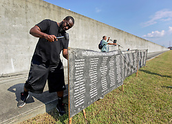 29 August 2015. Lower 9th Ward, New Orleans, Louisiana.<br /> Hurricane Katrina 10th anniversary memorial.<br /> Luther Adamson hammers wooden stakes holding banners containing the names of hurricane Katrina victims at the point in the levee which gave way a decade ago. <br /> Photo credit©; Charlie Varley/varleypix.com.