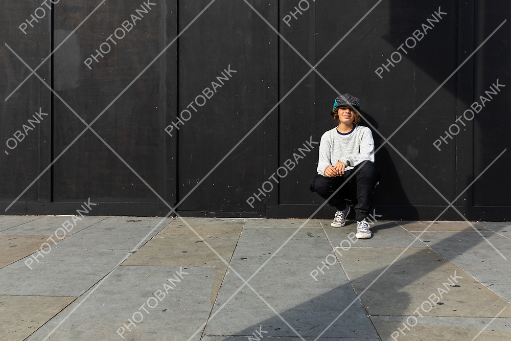 Young boy bent down to the ground with sneakers in London alley. Black background