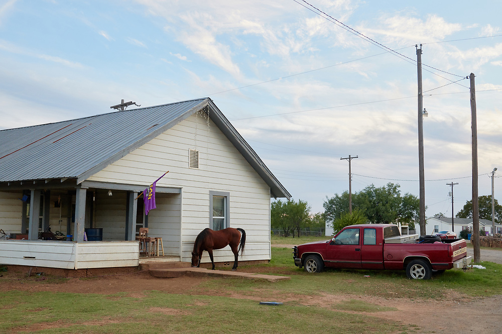 A horse stands outside a home in Moran, Texas on October 18, 2017. (Cooper Neill for The New York Times)