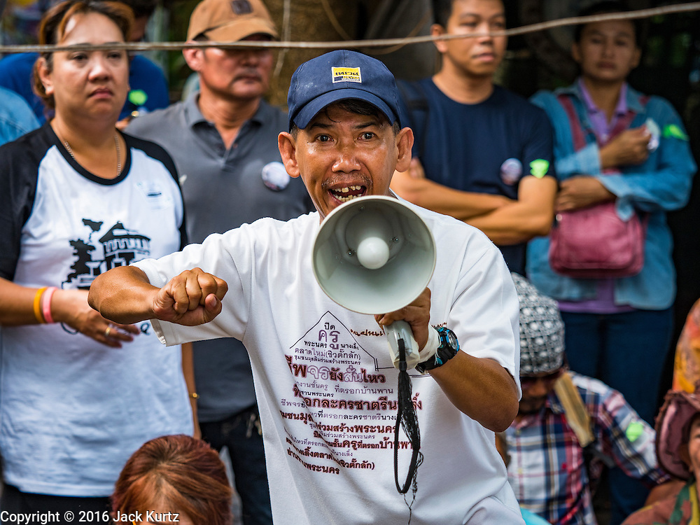 03 SEPTEMBER 2016 - BANGKOK, THAILAND:   LEK, a community leader in Pom Mahakan, uses a bullhorn to encourage residents to resist police during a forced eviction. Hundreds of people from the Pom Mahakan community and other communities in Bangkok barricaded themselves in the Pom Mahakan Fort to prevent Bangkok officials from tearing down the homes in the community Saturday. The city had issued eviction notices and said they would reclaim the land in the historic fort from the community. People prevented the city workers from getting into the fort. After negotiations with community leaders, Bangkok officials were allowed to tear down 12 homes that had either been abandoned or whose owners had agreed to move. The remaining 44 families who live in the fort have vowed to stay.    PHOTO BY JACK KURTZ