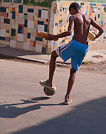 Boy playing soccer on way home from market, Chinatown, Havana, Cuba