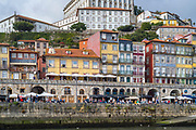 Riverside balconied homes and cafes in bright colours in Ribeira by the River Douro in Porto, Portugal