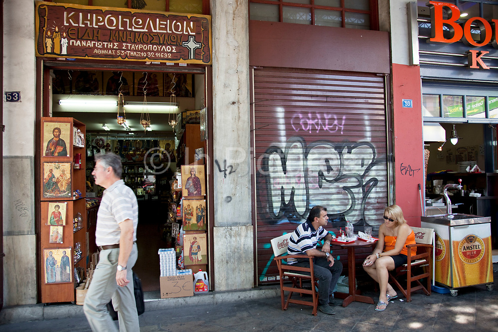 """Customers sitting outside a cafe next to a shop selling religious icons, paintings and pictures in the area of Omonia. Among religions in Greece, the largest denomination is the Greek Orthodox Church, which represents the majority of the population and which is constitutionally recognised as the """"prevailing religion"""" of Greece (making it one of the few European countries with a state religion). Other major religions include Catholicism, Islam and Protestantism. According to a 2005 Eurobarometer Poll, 81% of Greek citizens believe that there is a God, whereas 16% believed in some sort of spirit or life force and 3% responded that they did not believe there is any sort of God, spirit or life force. Athens is the capital and largest city of Greece. It dominates the Attica periphery and is one of the world's oldest cities, as its recorded history spans around 3,400 years. Classical Athens was a powerful city-state. A centre for the arts, learning and philosophy."""
