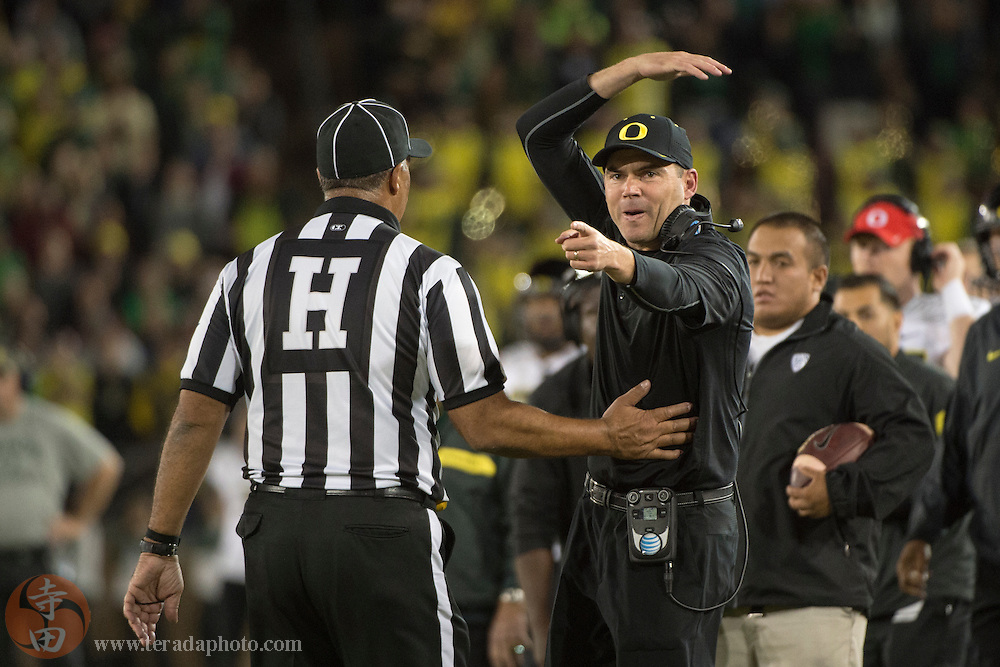 November 14, 2015; Stanford, CA, USA; Oregon Ducks head coach Mark Helfrich (right) argues with a referee during the fourth quarter against the Stanford Cardinal at Stanford Stadium. The Ducks defeated the Cardinal 38-36.