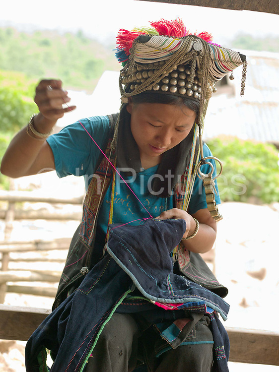 An Akha Nuquie woman sewing her traditional clothing in Ban Phanghok, Phongsaly province, Lao PDR. One of the most ethnically diverse countries in Southeast Asia, Laos has 49 officially recognised ethnic groups although there are many more self-identified and sub groups. These groups are distinguished by their own customs, beliefs and rituals. Details down to the embroidery on a shirt, the colour of the trim and the type of skirt all help signify the wearer's ethnic and clan affiliations.