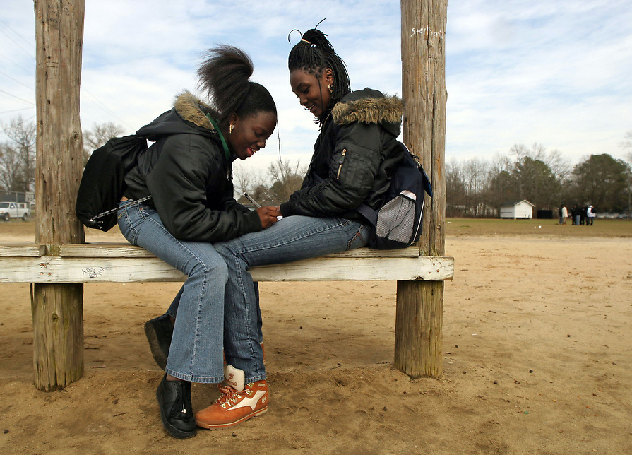 J.V. Martin Junior High School 7th graders, Tiqula Morrison and Justice Dixon, who have been best friends since kindergarten hang out at their favorite spot during their 15 minute break. The area designated for the students break is a mostly dirt field that has been used for athletic events and training since 1948.