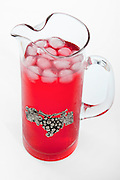 Cutout of a jug of cool and refreshing red raspberry juice and ice on white background