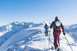 Rear view of skiers walking on ridge of mountain against sky