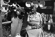 An elderly black woman weaves baskets by the roadside, South Carolina.