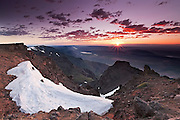 The rising sun begins to illuminate the east face of Steens Mountain in southeast Oregon. Steens Mountain is a roughly 30-mile (48-kilometer) long block mountain that rises a mile above the Alvord Desert. Massive internal pressure forced the ridge upward; glaciers carved dramatic gorges on the western face. Steens Mountain is the largest block-fault mountain in the Great Basin of Oregon and Nevada.