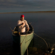 NHL player Jordin Tootoo anchors his boat after midnight in the summer light only a 100 miles from the Arctic Circle. Photographed for Sports Illustrated. <br /> <br /> Image available for licensing and for a personal print. Please Add To Cart and select the size and finish. All prints are delivered directly to you from the printer.