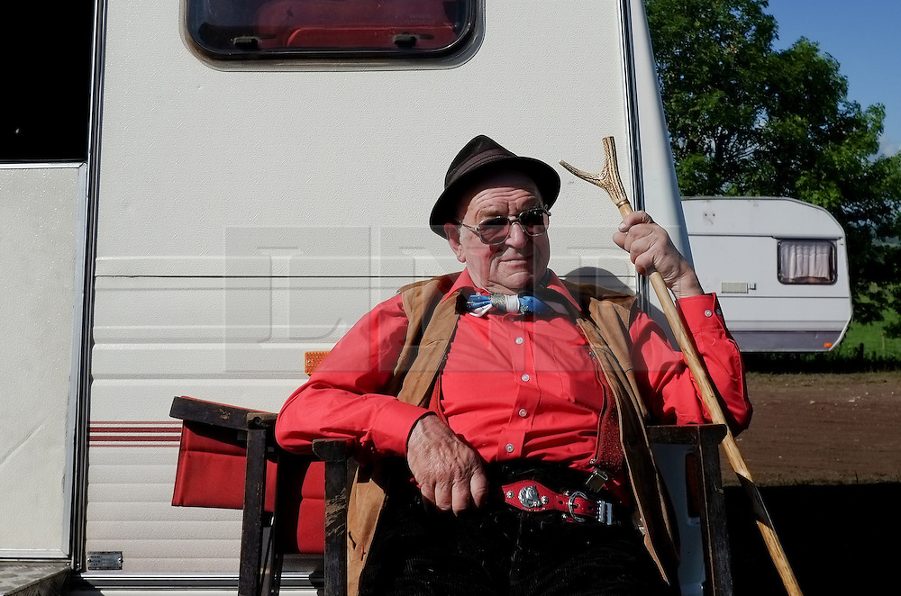© Licensed to London News Pictures. <br /> 06/06/2014. <br /> <br /> Appleby, Cumbria, England<br /> <br /> A man sits outside his caravan as gypsies and travellers gather during the annual horse fair on 6 June, 2014 in Appleby, Cumbria. The event remains one of the largest and oldest events in Europe and gives the opportunity for travelling communities to meet friends, celebrate their music, folklore and to buy and sell horses.<br /> <br /> The event has existed under the protection of a charter granted by King James II in 1685 and it remains the most important event in the gypsy and traveller calendar.<br /> <br /> Photo credit : Ian Forsyth/LNP