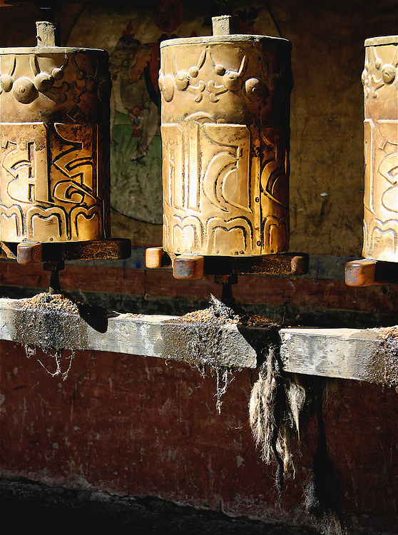 these are tibetan prayer wheels lining a wall of a monastery in lhasa tibet. Praying pilgrims walk along the wall spinning the wheels as they pray sending the prayer out into spirit.