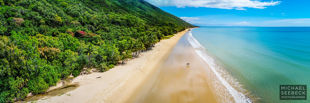 A low aerial view of a couple walking along Ellis Beach, one of Cairns' northerm beaches in Far North Queensland.<br /> <br /> Open Edition Print / Stock Image