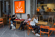 Customers and a pet dog sit outside a wok bar in the Slovenian capital, Ljubljana, on 25th June 2018, in Ljubljana, Slovenia. Slovenia is thought by many to be the most dog-friendly country in Europe and pets are welcome in most restaurants, shops, cafes, public spaces, and parks.