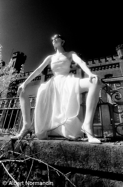Long white dress sitting on fence with sunglasses - One Woman Show