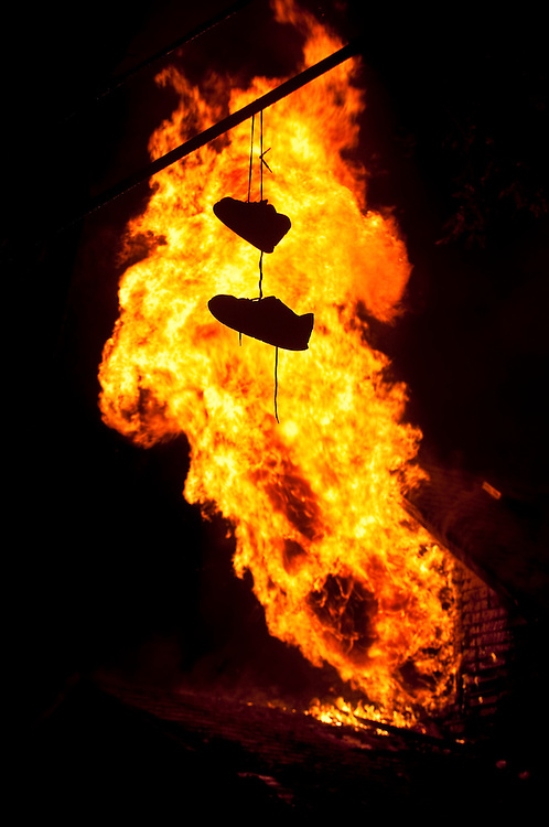 A pair of shoes is silhouetted as flames shoot out of a second story window of a burning home at Mable Avenue near Iowa Avenue in Flint Wednesday evening. The occupants moved out just a few days before according to officials. The home was allowed to burn down after conditions became too dangerous for firefighters to work inside.