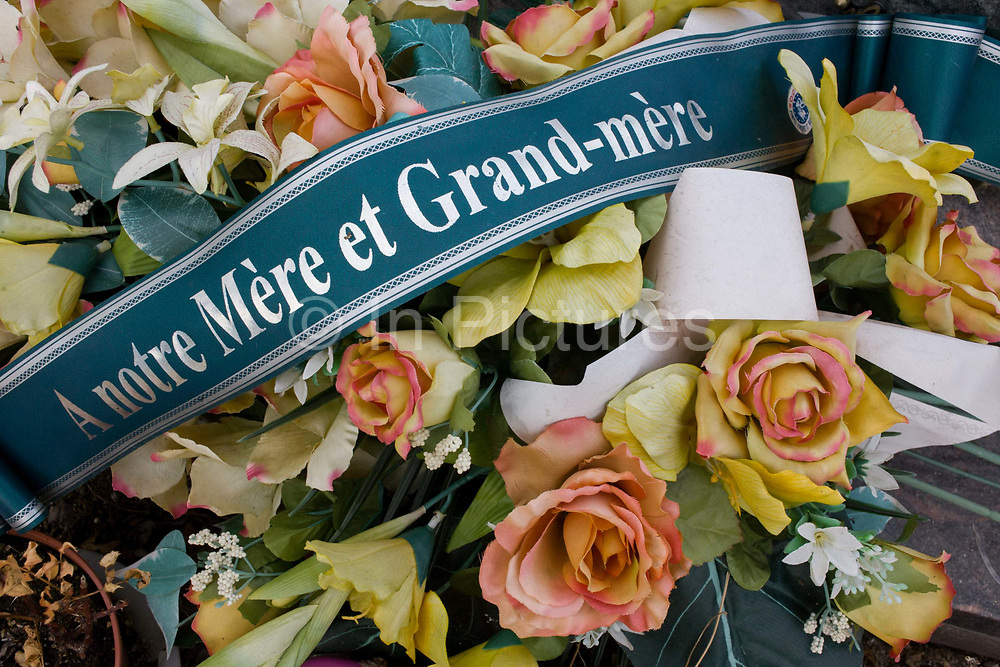 """Detail of wreaths to a mother and grandmother on a recent grave in a rural french hamlet in Indre-et-Loir. The French inscription reads """"To our mother and grandmother"""" and faded flower petals surround the ribbon."""