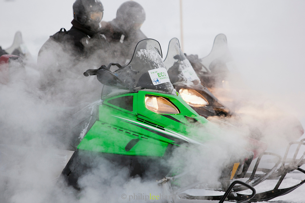 Snowmobiles warm up and rev their engines before setting off on a days expedition in Spitsbergen, Svalbard archipelago in the Arctic Circle, Norway