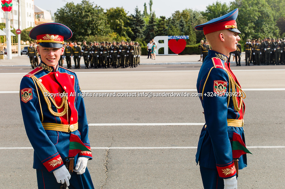 20150831 Moldova, Transnistria,Pridnestrovian Moldavian Republic (PMR) Tiraspol. Rehersal for the big parade, in the 25th  Transnistrian independance day when  they had a war separating from Moldova.young soldiers with transnistrian flags on their rifal waiting. I love Transnistria sign in the background.