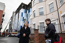 """© Licensed to London News Pictures. 16/11/2019. Bolton, UK. SANDRA RUIZ and TIAGO ALVES of Grenfell United, both of whom are former Grenfell Tower residents , at the site of the blaze . Firefighters work at the scene where a fire broke out overnight (15th/16th November 2019) at a block of flats known as """" The Cube """" , in Bolton Town Centre . At least two people are known to have been treated by paramedics at the scene of the six-story block , which is occupied by students of the University of Bolton . Photo credit: Joel Goodman/LNP"""