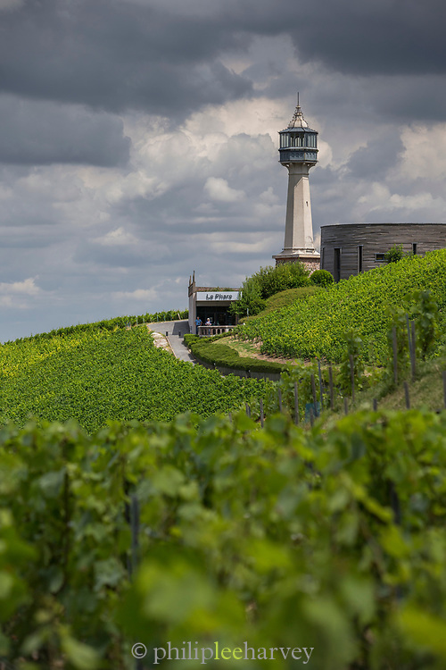 View of lighthouse and vineyards on hill under overcast sky, France