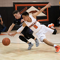 Miyamura Patriots point guard Jason Cordova (22) and Seth Manuelito (5) of the Gallup Bengals reach for the loose ball during the 4A -District Tournament Championship game at Gallup High School Saturday.