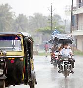 Motorcyclists holding umbrellas during the monsoon rains, Cochin, Kerala, India