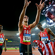 Jeremy Wariner of the United States, center, caught an American flag tossed from the stands as Wariner and men's 4 X 100m relay gold medalists Angelo Taylor, left, and David Neville, right, celebrated their victory at National Stadium on August 23, 2008 during the 2008 Summer Olympic Games in Beijing, China. (photo by David Eulitt / MCT)