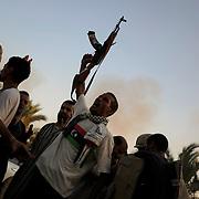 A group of rebel fighters celebrate the successful take of Muammar Gaddafi's Bab Al Azizia compound in Tripoli.