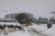 A country road is cleared of snow on 14th of January 2021 in Stow, Scottish Borders,United Kingdom. The snow has been falling all night and morning and the landscape is covered in the first real snow of the year. The Lauder Road runs across the moors between Stow and Lauder and the road is an important connection between the towns.