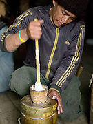 A Brokpa farmer hand churn's cow's milk to make into butter, Thagthi village, Eastern Bhutan. The Brokpa are a semi-nomadic tribe whose source of livelihood is dependent on yaks and sheep, the products of which they trade with neighbouring villages for daily necessities.