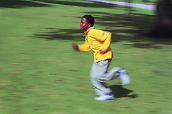 Young boy running across park,