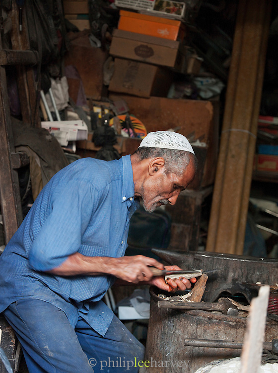A man chiseling a wooden handle in his workshop in the medina of Fes, Morocco