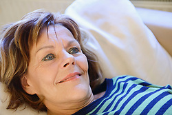 Senior woman relaxing and daydreaming on couch, smiling