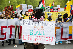 London, UK. 22nd May, 2021. An activist wearing a keffiyeh and holding a sign reading Palestinians for Black Liberation takes part in the National Demonstration for Palestine. It was organised by pro-Palestinian solidarity groups in protest against Israel's recent attacks on Gaza, its incursions at the Al-Aqsa mosque and its attempts to forcibly displace Palestinian families from the Sheikh Jarrah neighbourhood of East Jerusalem.