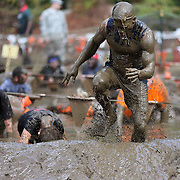 Competitors emerge from the mud pit during the New York Merrell Down and Dirty Obstacle Race presented by Subaru. Over 6000 competitors took part in the event which included mud pits, water crossings, slippery mountain, cargo nets, monster climb and ladder walls. The event was held at Pelham Bay Park The Bronx, New York. 29th September 2013. Photo Tim Clayton