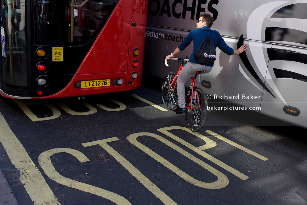 An urban cyclist leans against a tour coach in central London.