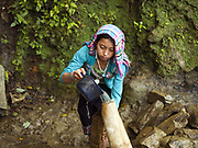 In the remote and roadless Akha Nuquie ethnic minority village of Ban Chakhampa, Phongsaly Province, Lao PDR, young girls first task of the day is collect water using a plastic scoop and carry it back to the village in traditional bamboo water carriers. Although there is a small basic school in Ban Chakhampa, it is still rare for girls in such remote villages to go to school because they are required to help their families with jobs at home.