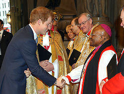 Prince Harry shakes hands with Archbishop Desmond Tutu as he arrives at Westminster Abbey in London for a memorial service for the former South African president Nelson Mandela.